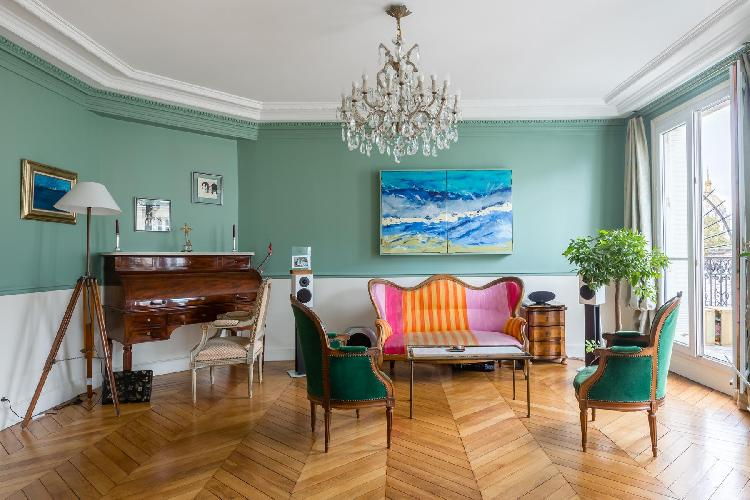 elegant living room with fine cornice and moldings, a piano, a stereo system, artworks, a plush chan