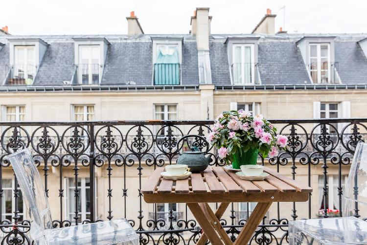 balcony with coffee table and 2 ghost chairs overlook the street below in Paris luxury apartment