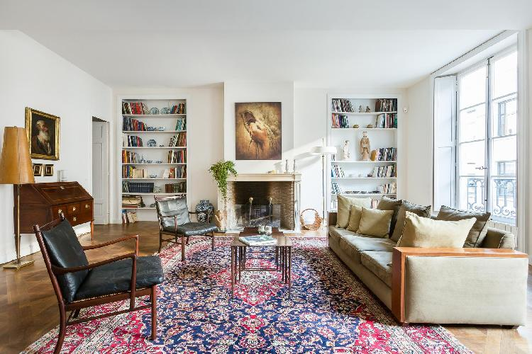 classic antique-filled living room with lots of stylish armchairs in Paris luxury apartment