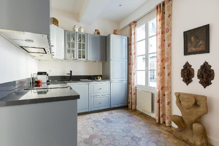 well-equipped kitchen with grey-colored cabinets, some antique artifacts, and light-colored drape in