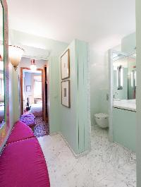 marble-tiled toilet in soft green hue in Paris luxury apartment