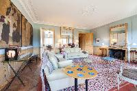 elegant living room with soft cream sofas surrounded by huge mirrors and framed artworks in Paris lu