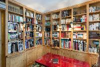 shelf-filled with books with red glossy study table in Paris luxury apartment