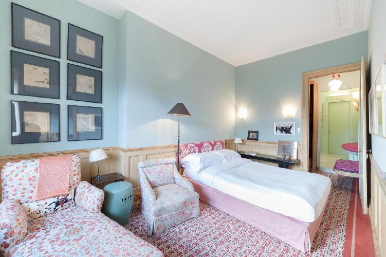 powder-blue walled bedroom with blossoming printed sofa chair and carpet rug in Paris luxury apartme
