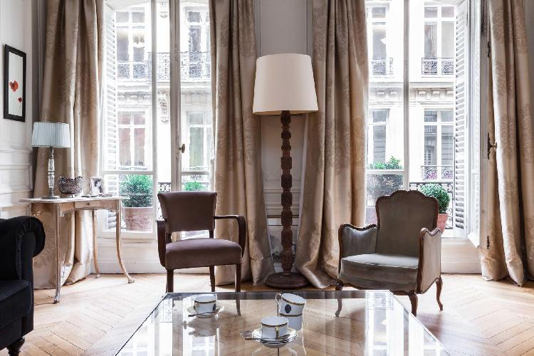 elegant living room with mismatched chairs and cosy mahogany accents in Paris luxury apartment