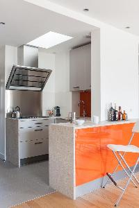modern well-equipped kitchen with a tangerine breakfast bar in Paris luxury apartment