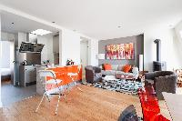 zesty open-plan living and dining area with glossy floorboards, graphic-print rugs, walls painted a