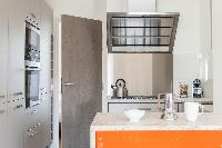 modern well-equipped kitchen with a concrete worktop and a sky-lit stove in Paris luxury apartment