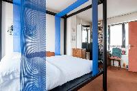 second bedroom with four-poster bed woven with blue streaming banners in Paris luxury apartment