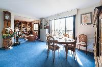 classic dining area with metal-studded, round walnut table and cerulean carpet rug in Paris luxury a