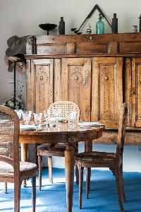 classic dining area with honeyed wood cabinet and cerulean carpet in Paris luxury apartment