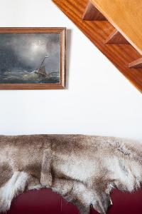animal rug on top of sofa beneath the wooden stairs in Paris luxury apartment