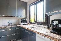 gray well-equipped kitchen in Paris luxury apartment