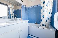 sleek bath in cerulean hues in Paris luxury apartment