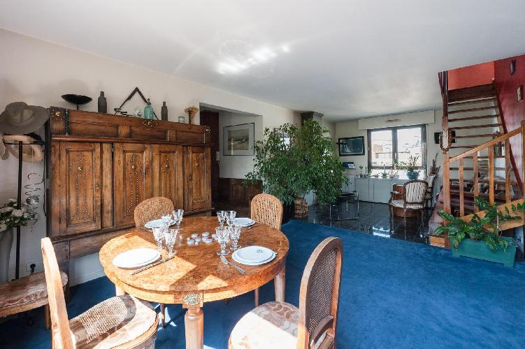 classic dining area with metal-studded, round walnut table and cerulean carpet in Paris luxury apart
