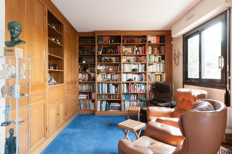 leather armchairs and library of books in Paris luxury apartment