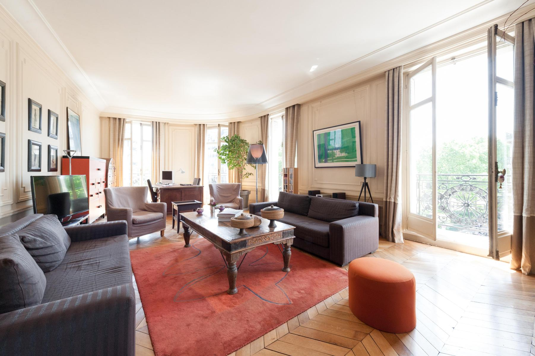 large 3-bedroom Paris luxury apartment with gry sofas and cream armchairs