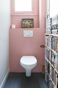 pretty in pink toilet with bookshelves in Paris luxury apartment