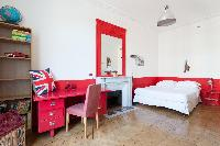 lively scarlet-and-white walled bedroom with fuchsia study desk, scarlet elaborate mirror on top of