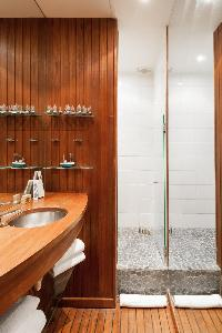 shower area with wooden sink countertop, wall, and floor in Paris luxury apartment