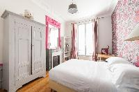 pretty in pink bedroom with floral wall paper in Paris luxury apartment