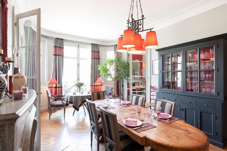 melange of vintage and modern pieces dining area with glass-paneled doors in Paris luxury apartment