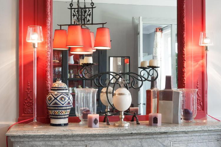 scarlet elaborate mirror on top of a marble fireplace in Paris luxury apartment