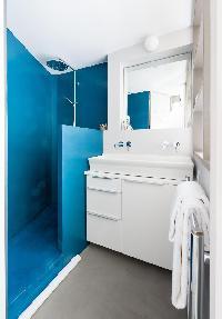 en suite bathroom with waterfall shower and aquamarine walls in Paris luxury apartment