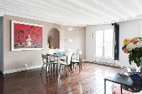 cozy dining area with wide framed artwork, glass dining table surrounds with 6 chairs in Paris luxur