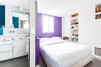 warm purple master bedroom and en suite bath in Paris luxury apartment