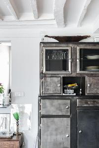exposed beams and industrial kitchen cabinet in Paris luxury apartment
