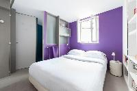 warm purple master bedroom with chrome lamps angled from designer bedside tables in Paris luxury apa