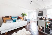 double bedroom with exposed beams, bed full of colorful cushions, and potted plants in Paris luxury