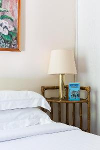 white-and-gold lamp beside a comfy bed in Paris luxury apartment