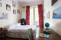 characterful bedroom with intriguing collection of furniture and artworks – from ornate wardrobes an