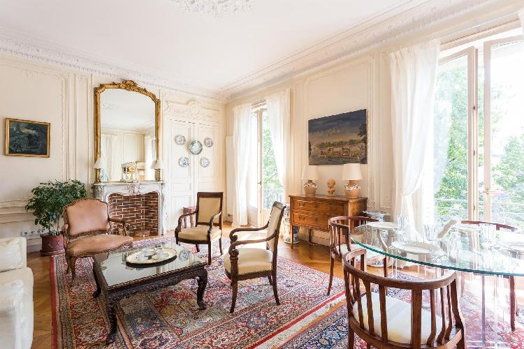elegant sitting room with the carved coffee table and dining table for 4 perch atop two richly patte