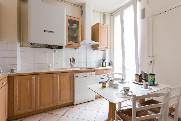 well-equipped kitchen with dining table for 4 in Paris luxury apartment