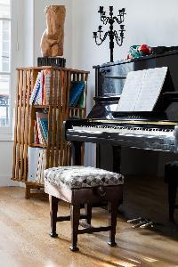 glossy dark wood piano in Paris luxury apartment