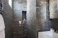 sleek gray-tiled shower area in Paris luxury apartment