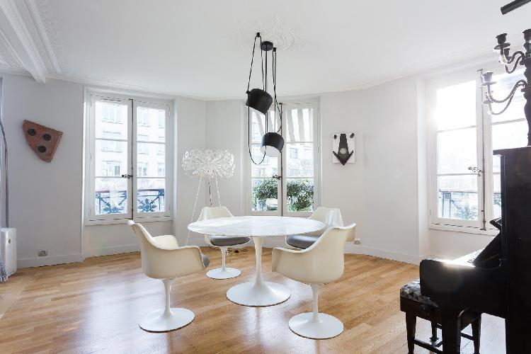 white dining table and 4 whitechairs beneath a black ceiling lamp in Paris luxury apartment