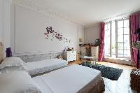 cozy bedroom with 2 single beds, chairs, table, cabinet, and tall window dressed in drape curtains i