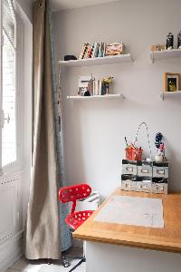 wooden study desk with red chair and drape curtain in a 4-bedroom Paris luxury apartment