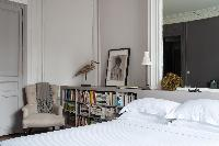 queen size bed, book shelves, armchair, and elaborate mirror in a 4-bedroom Paris luxury apartment