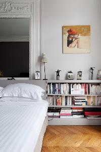 queen size bed and book shelves in a 4-bedroom Paris luxury apartment