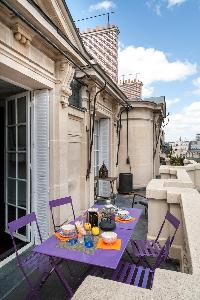long balcony with a lofty outdoor dining area in a Paris luxury apartment