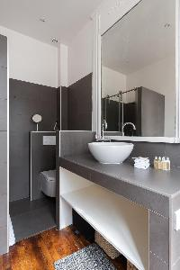 grey and white bathroom with sink and toilet in a 4-bedroom Paris luxury apartment