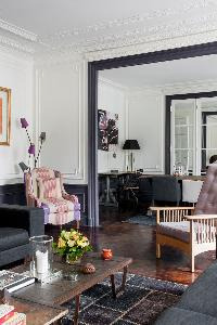 sitting room with clean-cut sofas, ornamental fireplace, and exuberant artworks in a Paris luxury ap