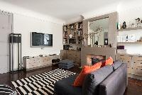 second sitting room with plump-cushioned chaise longue and a jazzy rug in a 4-bedroom Paris luxury a