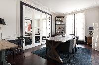stylish dining area with wooden table with 8 seating, grey carpet rug, study desk, and French doors
