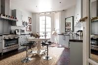 sophisticated kitchen with kitchen bar and stools in a 4-bedroom Paris luxury apartment